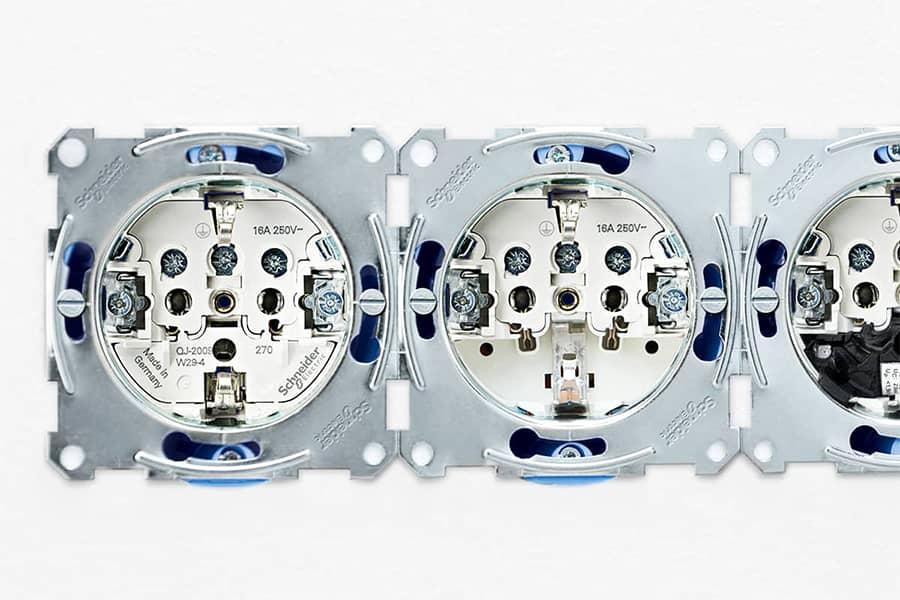 Drie sokkels van Schneider Electric stopcontacten naast elkaar