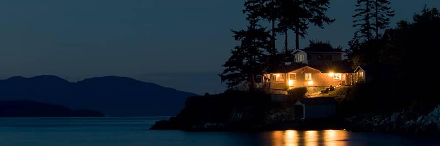 Huis aan het water met buitenverlichting in het donker