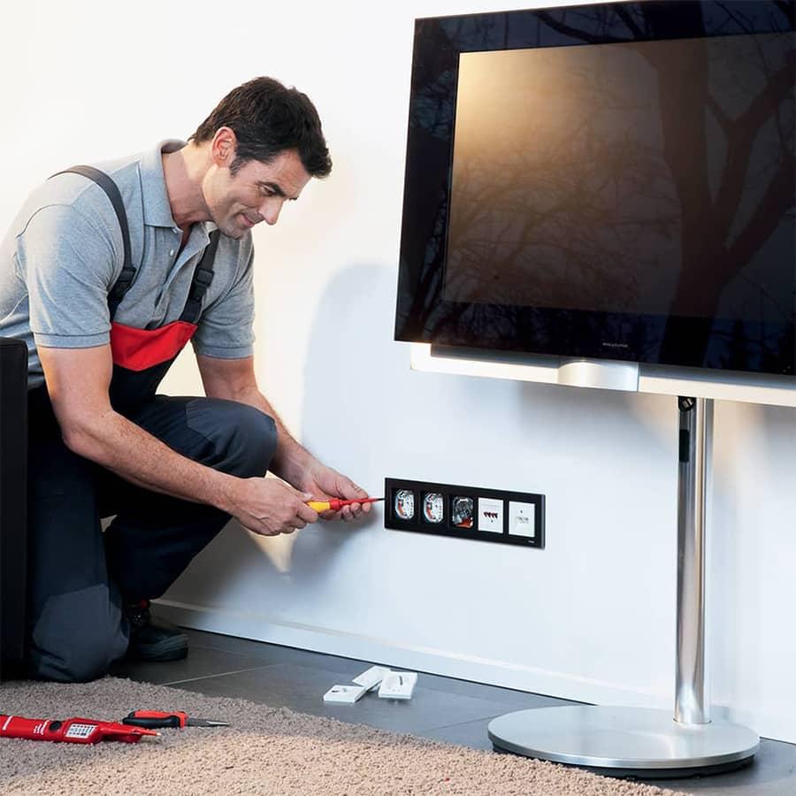 Installateur plaatst stopcontacten bij televisie