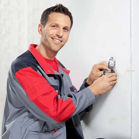 Man installeert Schneider Electric stopcontact in de muur