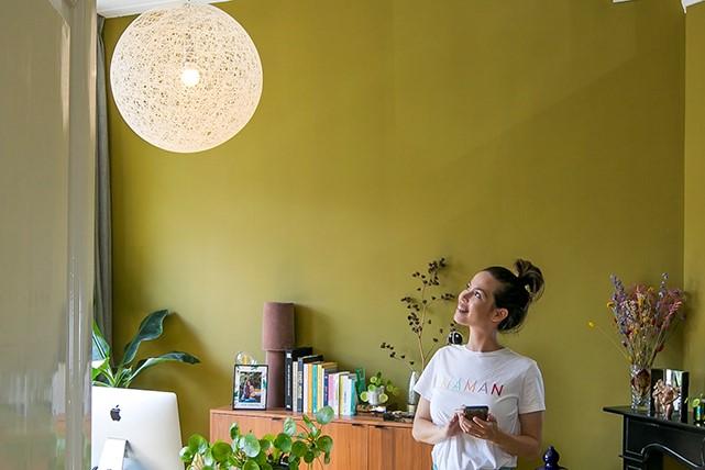 Jonge vrouw met wit T-shirt die in de  woonkamer naar haar designlamp kijkt