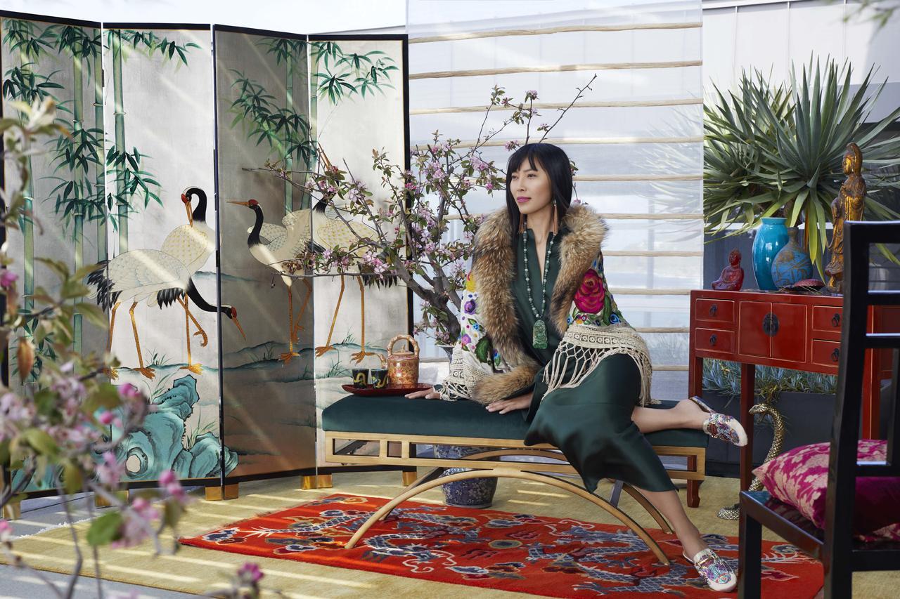 Japanse vrouw poseert zittend op een bankje in een kamer die de Japanse cultuur uitstraalt